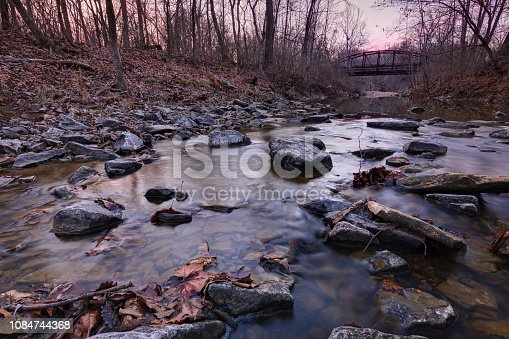 A rocky river bed with walking bridge in the distance. Grindstone Creek and nature area in Columbia, Missouri.