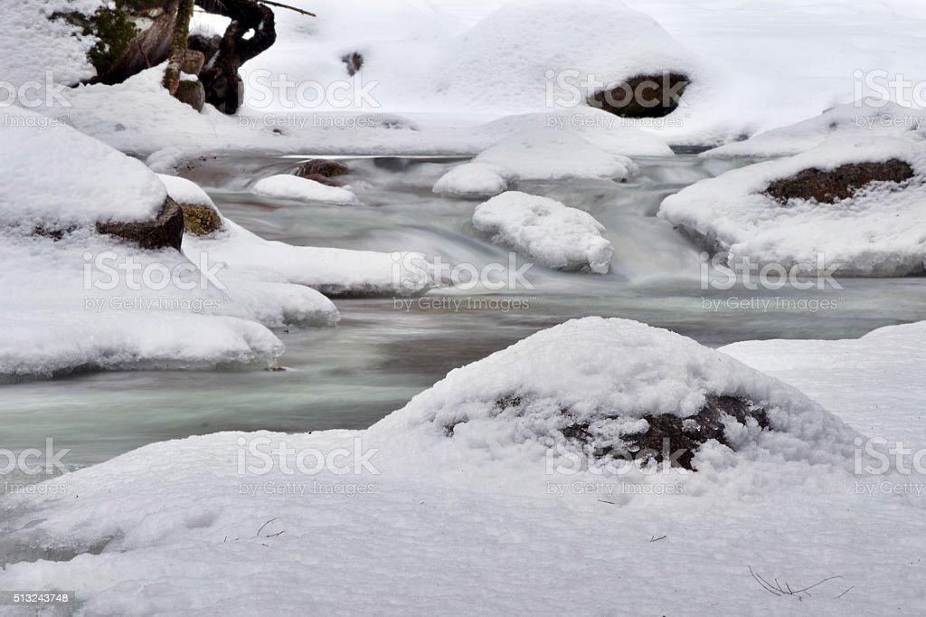 Rocky River Snakes Down Frozen Mountainside stock photo