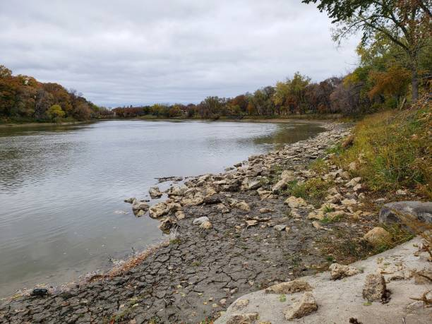 Rocky riverbank along the Assiniboine River in Winnipeg, Manitoba Rocky riverbank along the Assiniboine River in Winnipeg, Manitoba during late autumn riverbank stock pictures, royalty-free photos & images