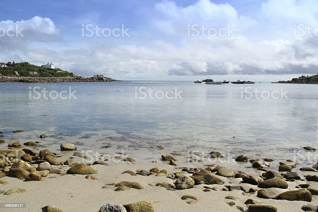 rocky sandy Beach picturesqe looking out to calm sea stock photo