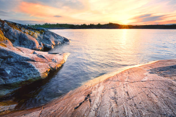 Rocky shore in the water Rocky shore in the water at sunset republic of karelia russia stock pictures, royalty-free photos & images