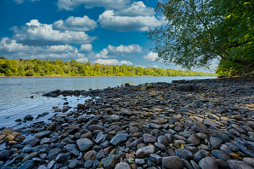 The rocky shore of the Delaware River at Giving Pond boat launch in Tinicum, Pennsylvania, USA.