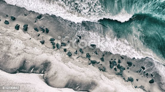 The sea with waves and ripples and the shore with rocks. This image was photographed from above with a drone.