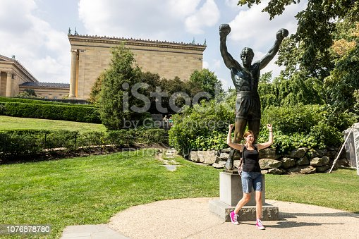 Philadelphia, Pennsylvania. Tourist posing with the Rocky statue, a movie memorial close to the 72 Rocky steps before the entrance of the Philadelphia Museum of Art