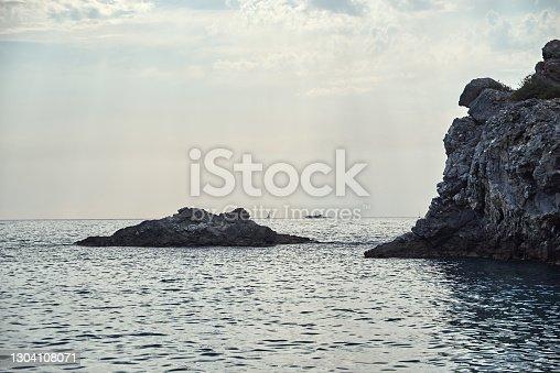 Rocky steep coast of the calm Mediterranean Sea, cloudy blue sky