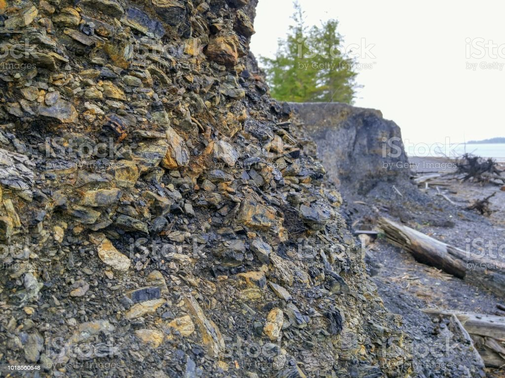 A rocky wall crumbles beside the ocean stock photo