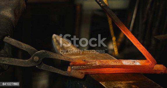 istock Rod hot iron on the anvil. 641027860