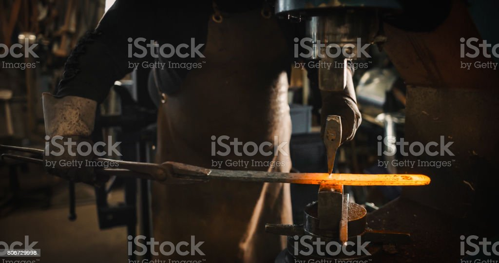 Rod hot iron on the anvil. stock photo