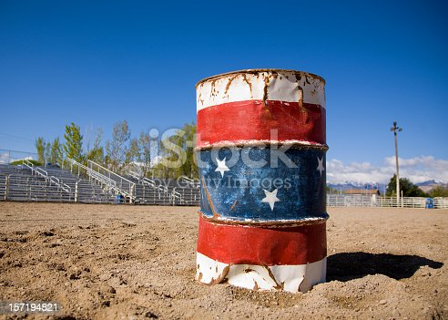 A red white and blue colored rodeo clown barrel in the middle of a rodeo arena.  The barrel is well used and rather beaten up. Empty bleachers and a gradient blue sky are visible in the background.