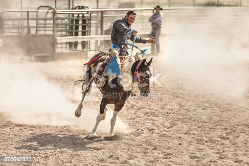 Stock photo of cowboys riding in the bareback event at a rodeo stadium in Utah