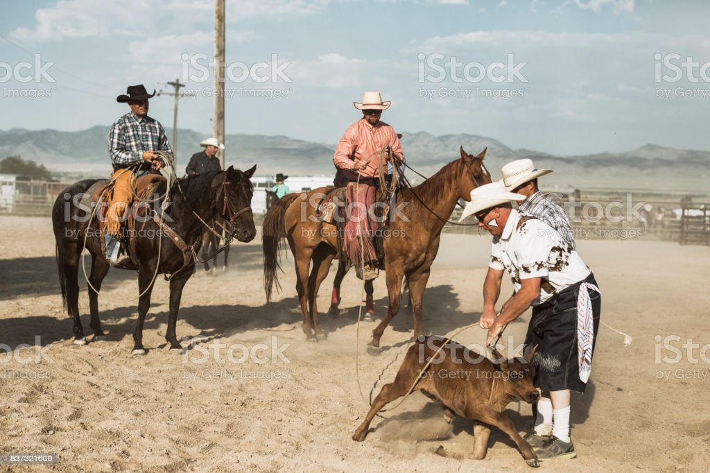 A rodeo clown holding the rope around a calf, while two mounted cowboys and one standing by are all watching him. stock photo