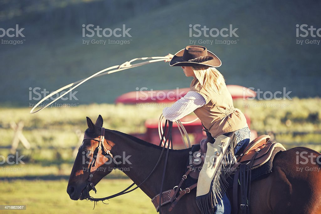 Rodeo cowgirl using lasso while performing stunt stock photo