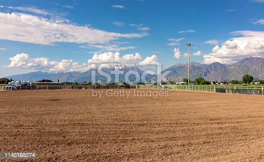An empty rural rodeo paddock, with a prepared soil base, surrounded by the Rocky mountains.