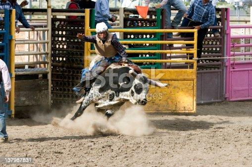 High school rodeo boy rides a bucking bull.