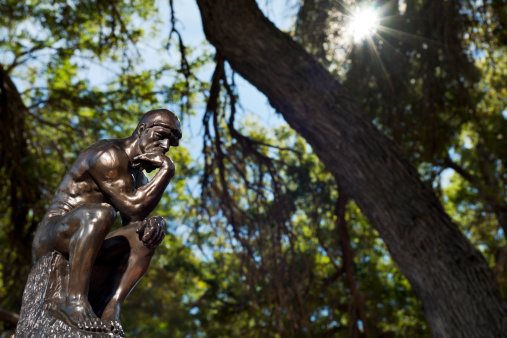 View of a small bronze replica of Rodin's The Thinker statue, sitting in a spot of light in a forest.  The Thinker is often used to represent philiosphy.