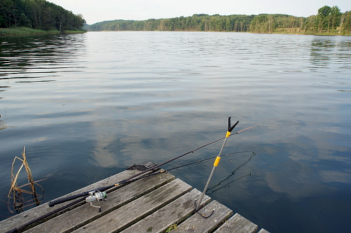 Rods lying on a wooden platform on the lake