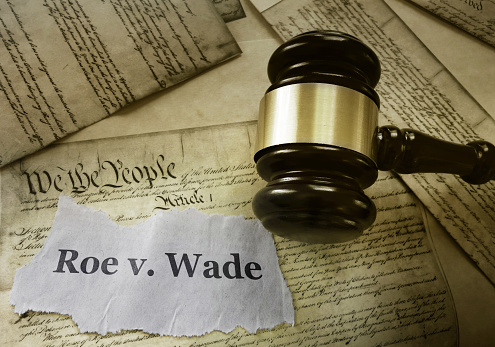 Roe v Wade news headline with gavel on a copy of the United States Constitution
