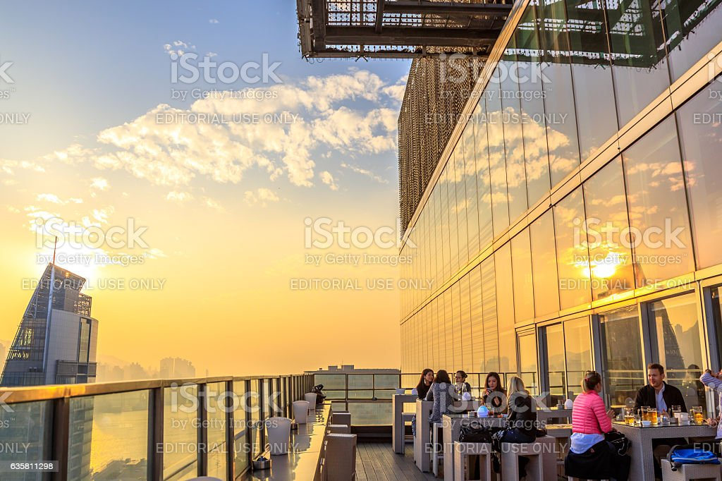 Roftop in Hong Kong Hong Kong, China - January 1, 2016: people drink and enjoy the skyline of Victoria Harbor at sunset from the rooftop of Eye Bar, inside iSquare shopping center on Nathan Road in Tsim Sha Tsui, Kowloon Aerial View Stock Photo