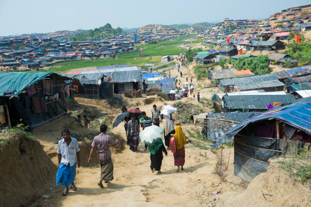 Rohingya housing at Jamtoli refugee camp Jamtoli refugee camp, Bangladesh - October 26, 2017: Rohingya Muslims walk down a dirt lane in the crowded Jamtoli refugee camp near Cox's Bazar, Bangladesh. rohingya culture stock pictures, royalty-free photos & images