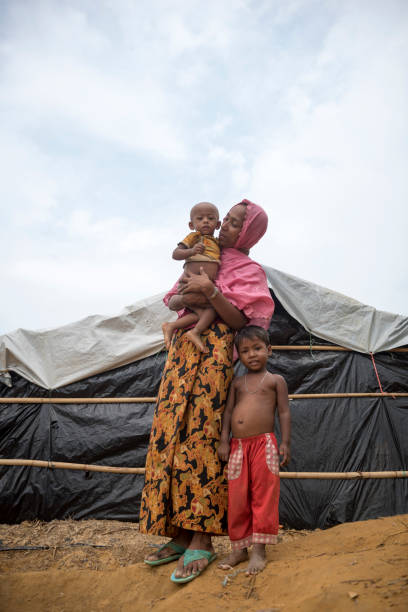 Rohingya mother and children in refugee camp A 25-year-old Rohingya Muslim woman stands with two children outside a shelter in the sprawling Kutupalong refugee camp in Bangladesh. They are among the 600,000 who fled Myanmar in the two months beginning August 25. (October 29, 2017) rohingya culture stock pictures, royalty-free photos & images
