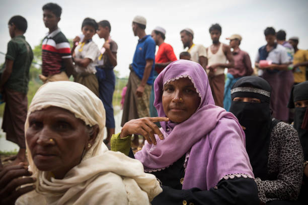 Rohingya Muslim men and women in Bangladesh Rohingya women and men wait in line for a humanitarian aid distribution at Chakmarkul refugee camp in Bangladesh. (October 28, 2017) rohingya culture stock pictures, royalty-free photos & images
