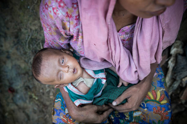 Rohingya Muslim mother and baby A Rohingya mother holds her two-month-old daughter outside their shelter at Jamtoli refugee camp near Cox's Bazar, Bangladesh (October 26, 2017) rohingya culture stock pictures, royalty-free photos & images