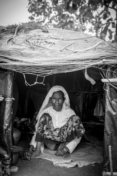 Rohingya Muslim woman living in rustic shelter Jamtoli refugee camp, Bangladesh - October 26, 2017: A Rohingya Muslim woman sits inside a rustic shelter at Jamtoli refugee camp near Cox's Bazar, Bangladesh. rohingya culture stock pictures, royalty-free photos & images