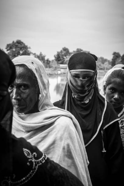 Rohingya Muslim women in Bangladesh Chakmarkul refugee camp, Bangladesh - October 28, 2017: Rohingya Muslims women wait in line for a humanitarian aid distiribution at Chakmarkul refugee camp in Bangladesh. Originally from Myanmar, hundreds of thousands of Rohingya Muslims are currently living in difficult conditions in southeastern Bangladesh. rohingya culture stock pictures, royalty-free photos & images