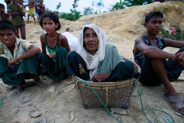 Rohingya Muslims Flee Violence In Myanmar Rohingya Muslims, who crossed over from Myanmar into Bangladesh, sits beside a road at Ukniya, Bangladesh, October 2, 2017. The United Nations' humanitarian office said Thursday that the number of Rohingya Muslims fleeing to Bangladesh since Aug. 25 has topped 500,000. rohingya culture stock pictures, royalty-free photos & images