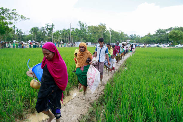 Rohingya Muslims Flee Violence In Myanmar Rohingya Muslims, who crossed over from Myanmar into Bangladesh, walks through muddy field to take shelter at Balukhali refugee camp, Bangladesh, October 2, 2017. The United Nations' humanitarian office said Thursday that the number of Rohingya Muslims fleeing to Bangladesh since Aug. 25 has topped 500,000. rohingya culture stock pictures, royalty-free photos & images