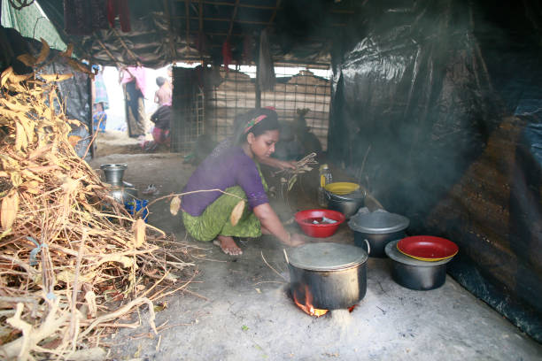 Rohingya Muslims Flee Violence In Myanmar Rohingya Muslim woman, who crossed over from Myanmar into Bangladesh, prepars meal for her family at Jamtoli refugee camp, Bangladesh, October 2, 2017. The United Nations' humanitarian office said Thursday that the number of Rohingya Muslims fleeing to Bangladesh since Aug. 25 has topped 500,000. rohingya culture stock pictures, royalty-free photos & images