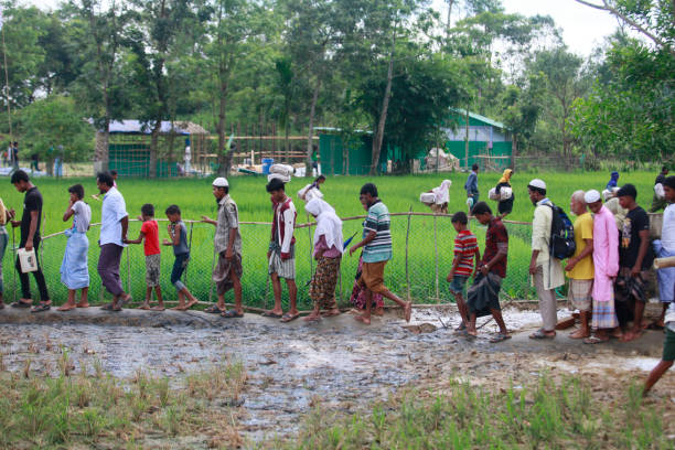 Rohingya Muslims Flee Violence In Myanmar Rohingya Muslims, who crossed over from Myanmar into Bangladesh, walks through muddy field after collecting aid from a distribution centre near Balukhali refugee camp, Bangladesh, October 2, 2017. The United Nations' humanitarian office said Thursday that the number of Rohingya Muslims fleeing to Bangladesh since Aug. 25 has topped 500,000. rohingya culture stock pictures, royalty-free photos & images
