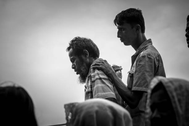 Rohingya Muslims in Bangladesh Chakmarkul refugee camp, Bangladesh - October 28, 2017: Rohingya Muslims wait in line for a humanitarian aid distiribution at Chakmarkul refugee camp in Bangladesh. Originally from Myanmar, hundreds of thousands of Rohingya Muslims are currently living in difficult conditions in southeastern Bangladesh. rohingya culture stock pictures, royalty-free photos & images