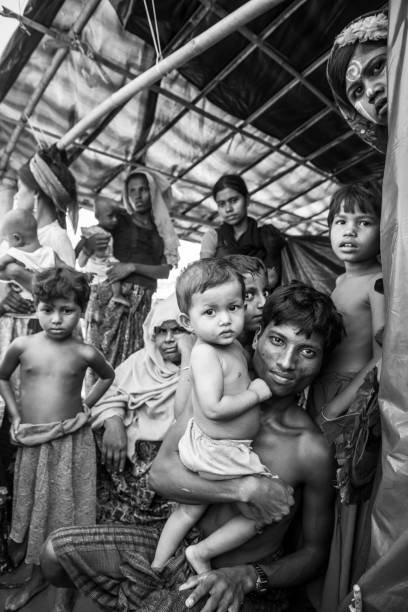 Rohingya Muslims in Bangladesh Rohingya men, women, and children, stateless and unemployed, shelter from the hot midday sun in a makeshift shelter at Jamtoli refugee camp in Bangladesh (October 27, 2017) rohingya culture stock pictures, royalty-free photos & images