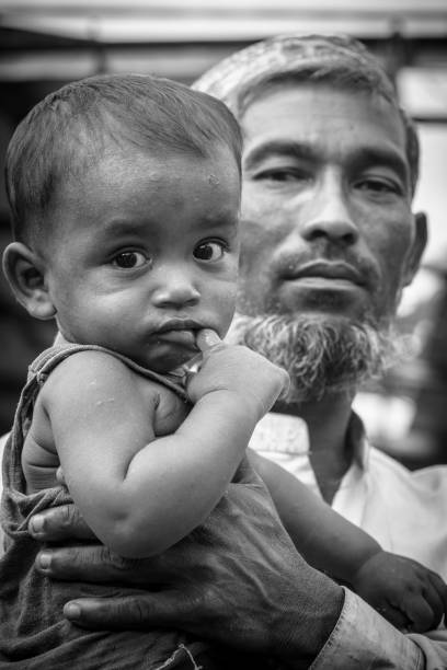 Rohingya Muslims in Bangladesh A Rohingy Muslim man holds a child outside a shelter in Kutupalong refugee camp in Bangladesh. (October 29, 2017) rohingya culture stock pictures, royalty-free photos & images