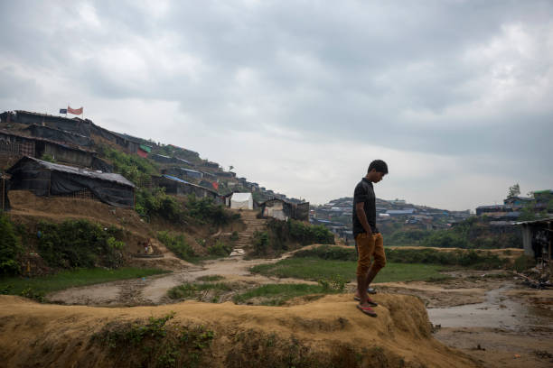 Rohingya refugee camp in Bangladesh A Rohingya refugee walks at the Chakmarkul (Pulonkhli) refugee camp near Cox's Bazar, Bangladesh. rohingya culture stock pictures, royalty-free photos & images
