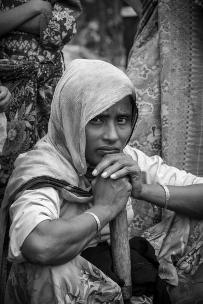Rohingya refugee in Bangladesh Black and white image of a Rohingya woman sitting outside her shelter at Kutupalong refugee camp near Cox's Bazar, Bangladesh (October 2017) rohingya culture stock pictures, royalty-free photos & images