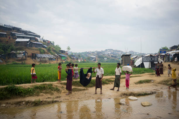 Rohingya refugee seeking medical care in Bangladesh Rohingya Muslims carry an ill member of their community in a hammock sling attached to a pole through Chakmarkul (Pulonkhli) refugee camp near Cox's Bazar, Bangladesh (October 28, 2017) rohingya culture stock pictures, royalty-free photos & images