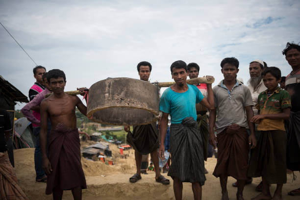 Rohingya refugees and toilet construction in Bangladesh Jamtoli refugee camp, Bangladesh - October 30, 2017: Two Rohingya men carry a concrete cylinder to use in the construction of a toilet pit in the refugee camp. rohingya culture stock pictures, royalty-free photos & images