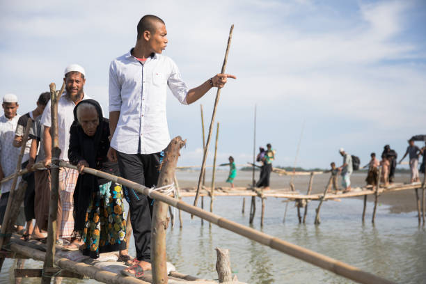 Rohingya refugees crossing bamboo bridge in Teknaf Rohingya refugees crossing bamboo bridge in Teknaf rohingya culture stock pictures, royalty-free photos & images