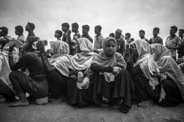 Rohingya refugees in Bangladesh Rohingya men and women wait in line for an aid distribution at Chakmarkul refugee camp, Bangladesh (October 28, 2017) rohingya culture stock pictures, royalty-free photos & images