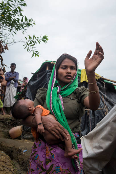 Rohingya refugees in refugee camp in Bangladesh A Rohingya woman holds her baby while talking with another person (not pictured) at Chakmarkul (Pulonkhli) refugee camp near Bangladesh's border with Myanmar. (October 28, 2017) rohingya culture stock pictures, royalty-free photos & images