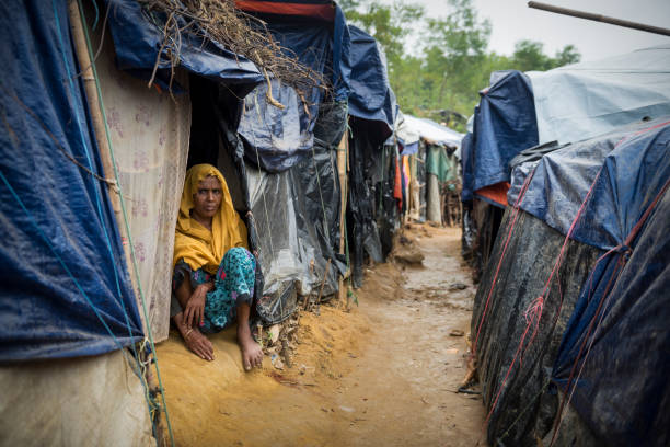 Rohingya woman and shelters at Kutupalong refugee camp in Bangladesh A woman, one of the 600,000 Rohingya who fled Myanmar in the two months beginning on August 25, 2017, sits at the entrance to her shelter in Kutupalong refugee camp in Bangladesh. (October 29, 2017) rohingya culture stock pictures, royalty-free photos & images