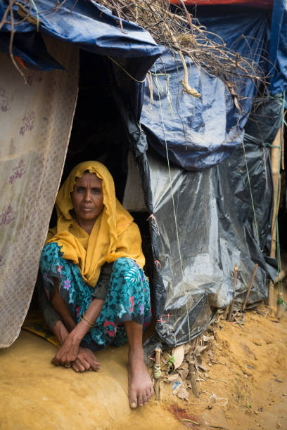 Rohingya woman and shelters at Kutupalong refugee camp in Bangladesh A woman, one of an estimated 600,000 Rohingya who fled Myanmar in late 2017, sits at the entrance to her shelter in Kutupalong refugee camp in Bangladesh. rohingya culture stock pictures, royalty-free photos & images