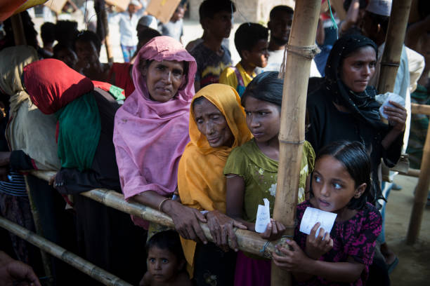 Rohingya women and children waiting for aid distribution in Bangladesh Rohingya women and children wait in line for a humanitarian aid distribution at Jamtoli refugee camp in Bangladesh. (October 26, 2017) rohingya culture stock pictures, royalty-free photos & images