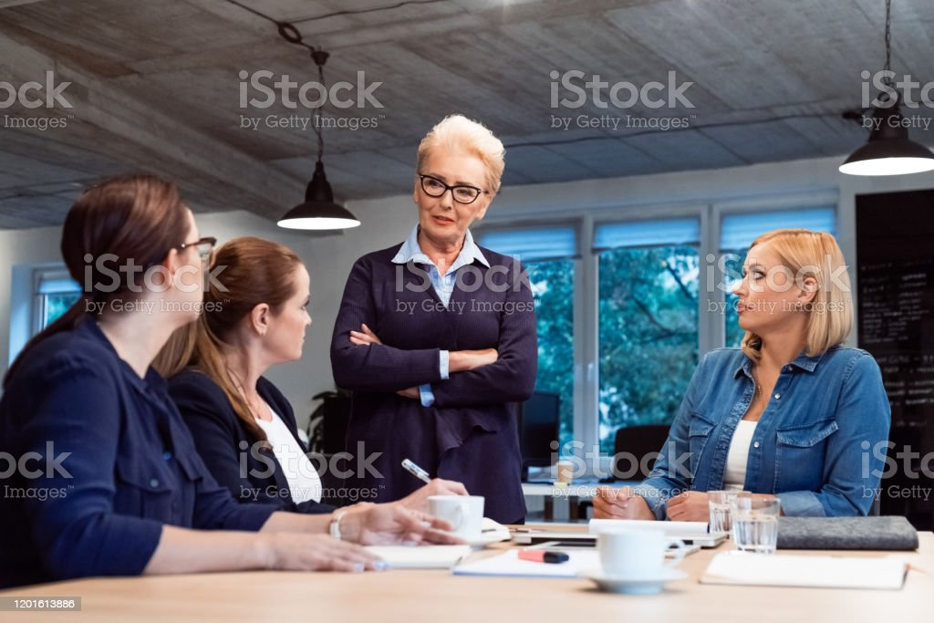 Role model planning with colleagues in office Confident role model advising businesswomen in new office. Female professionals are planning business strategy for start-up. They are discussing in meeting. 35-39 Years Stock Photo