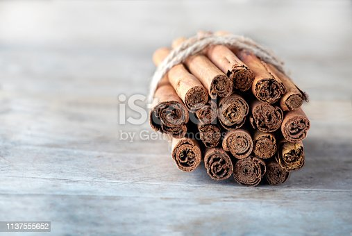 role of cinnamon  sticks in selective focus  on a light wooden table  tide with string  blurred background to ad copy space and text overlay