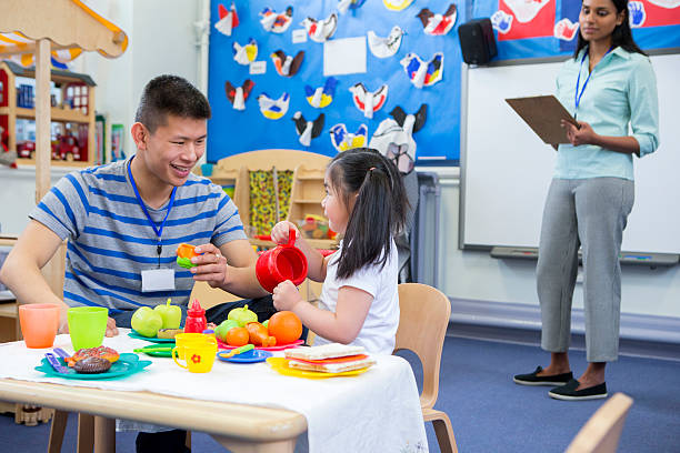 Roleplay Kitchen at Nursery Male teacher playing in a toy kitchen with a nursery student. There is a teacher in the background with a clipboard who is watching them. preschool teacher stock pictures, royalty-free photos & images
