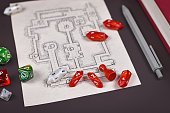 Roleplaying game dices on hand drawn dungeon adventure map. Concept for table top role playing games on dark background