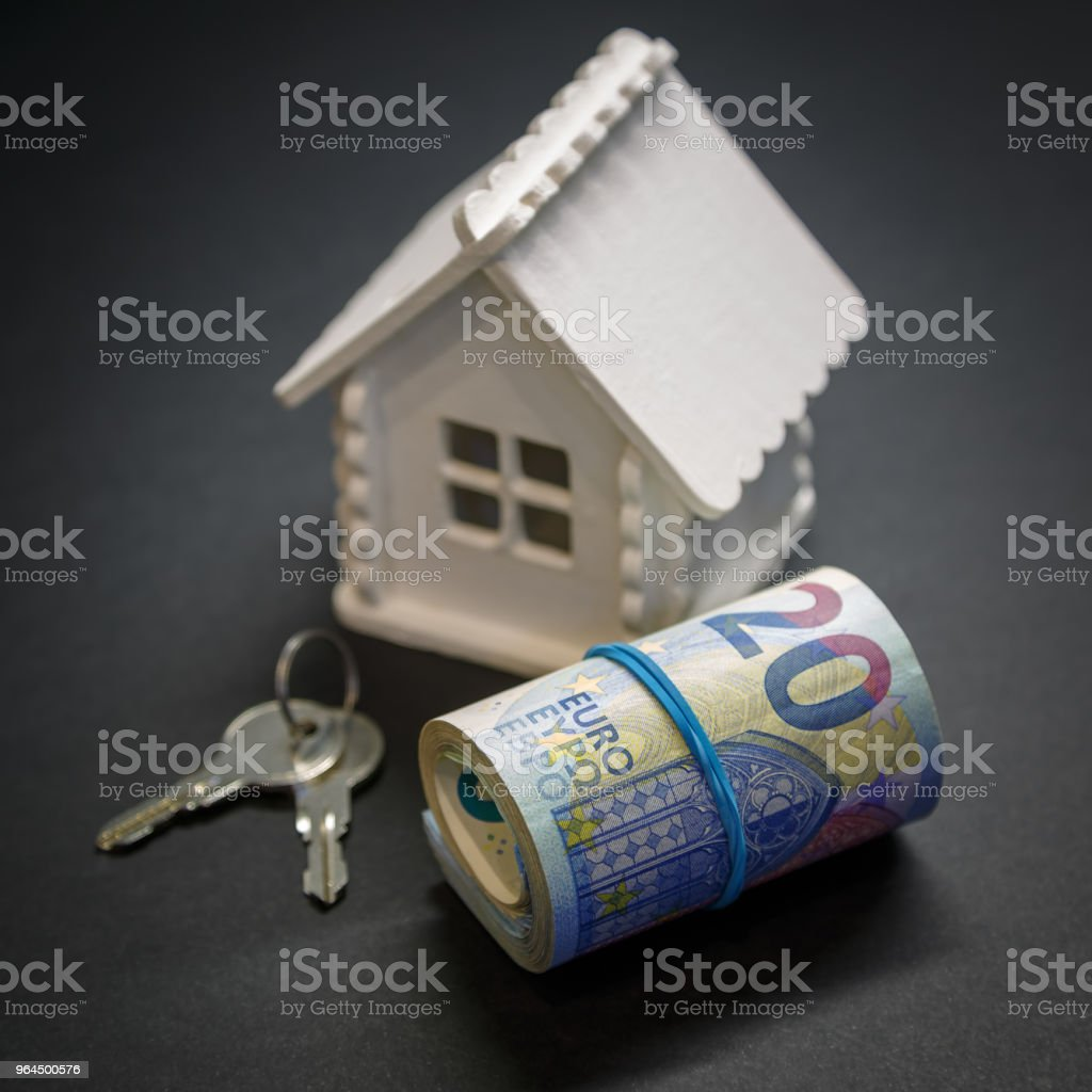 A roll consisting of euros, a house mock-up of white colour and keys to a future home on a black background stock photo